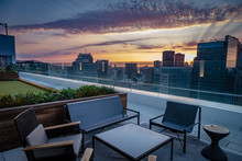 A Rooftop Deck With Chairs Overlooks The San Francisco Skyline Sunset With Purple And Gold Clouds