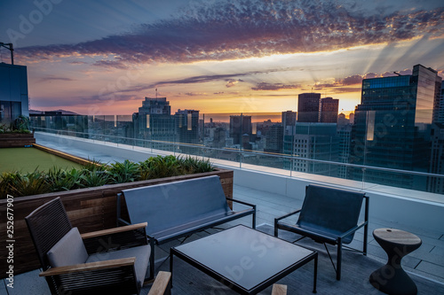 Fotografía A rooftop deck with chairs overlooks the San Francisco skyline sunset with purpl