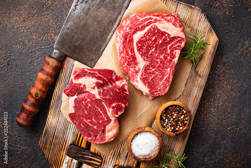 Canvastavla Raw marbled ribeye steak and butchers knife