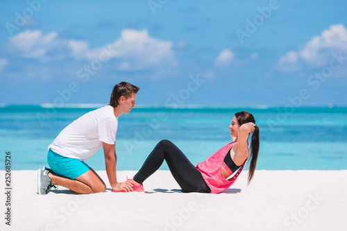 Fotografie, Obraz  Young couple do abdominal crunches on white beach during vacation