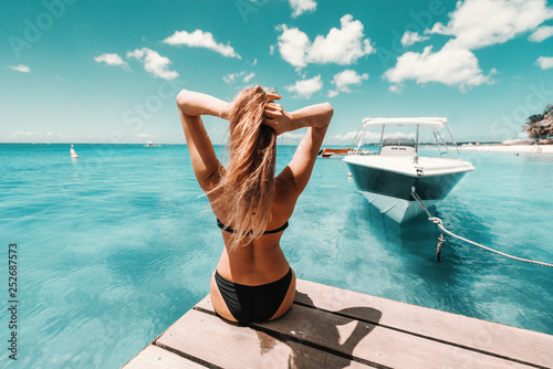 Fototapeta Beautiful shaped brunette in swimsuit an with sunglasses sitting on pier and enjoying sunny weather and ocean