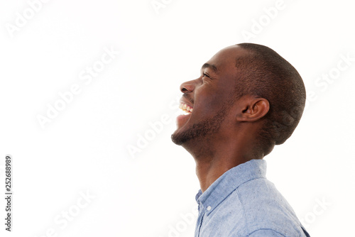 Fototapeta profile portrait of handsome young black man laughing against isolated white bac