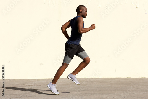 Full body profile of healthy young african american man running by wall