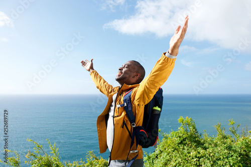happy young african american male traveler with arms open outdoors - fototapety na wymiar