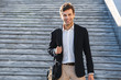Handsome young business man carrying bag