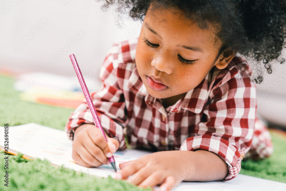 Fototapeta Cute young African American kid girl drawing or painting with colored pencil. Kindergarten children education, back to school, or preschool child study at home concept