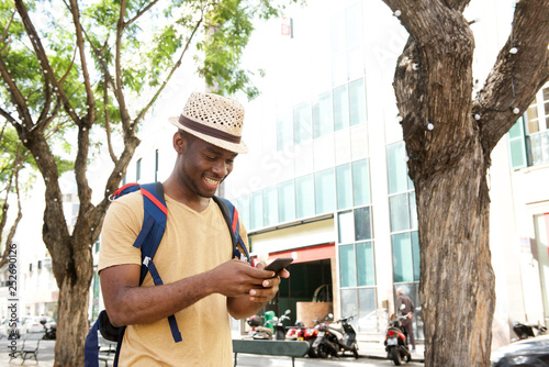 Fotografía  happy african american man with bag and hat walking with mobile phone outdoors