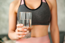 Woman In A Tracksuit Drinking A Glass Of Water