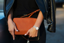 Luxurious Young Woman In Black Leather Jacket Holding Orange Purse