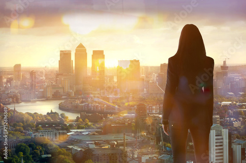 Fotografia  Young woman looking over the City of London at sun set