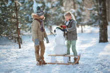 Children Build A Snowman. Boys Building A Snow Man Playing Outside On A Sunny Snowy Winter Day. Outdoor Family Holiday On The Christmas Holidays. Boy And Girl Playing Snowballs.