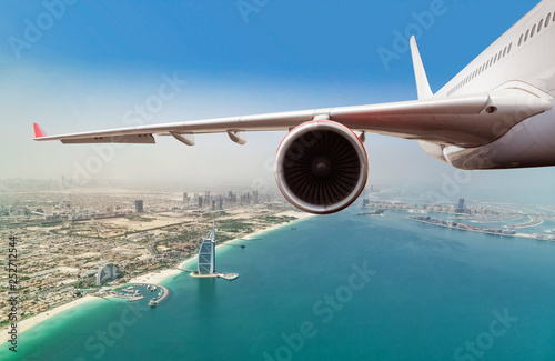 Fotografie, Obraz  Commercial jet plane flying above Dubai city.