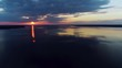 Aerial view. Amazing sky reflected in water. Beautiful sunset over the lake. landscape, in background horizon and forest. Orange or yellow sun penetrates through fluffy or airy gray or white clouds