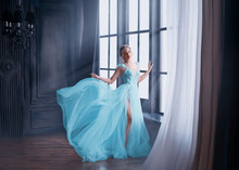 Gorgeous Image Of Graduate In 2019, Girl In Long Blue Gentle Flying Dress With Bare Leg Stands Alone, Fabulous Princess. Elegant Lady With Blond Hair In Sunlight Rays. Loft Style Interior Background