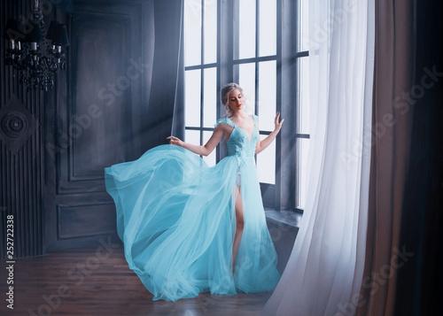 Fototapeta gorgeous image of graduate in 2019, girl in long blue gentle flying dress with bare leg stands alone, fabulous princess