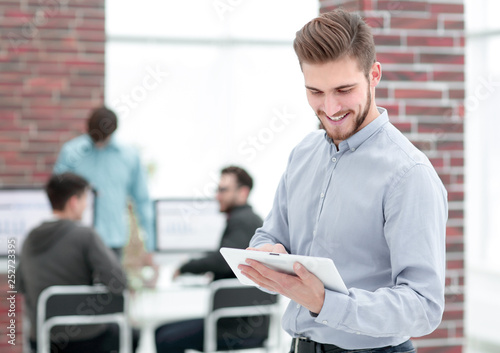 Handsome businessman using a tablet in the office.