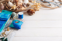 Sewing Accessories And Basket With Sea Shells On White Wooden Surface, Space For Text