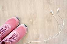 Fitness Accessories Pair Of Pink Pastel Sport Running Shoes With White Earphones (Headphones) On Wooden Floor. Woman Sportswear. Top View Of Pink Sneakers Isolated On Wood Background, And Copy Space.