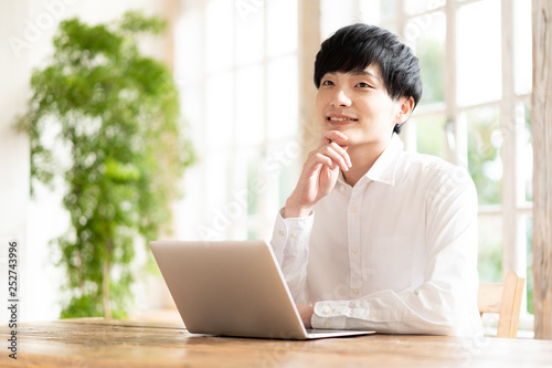 Fotografie, Obraz  young asian man using laptop in living room