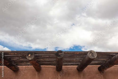 Fotografie, Obraz  Wide view detail of red adobe exterior with beans, wood slats, blue sky with clo