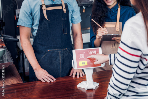 Valokuva  customer self service order drink menu with tablet screen at cafe counter bar,seller coffee shop accept payment by mobile