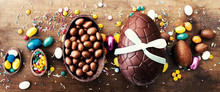 Beautiful Creative Photo With Chocolate Easter Eggs On Wooden Background. Happy Easter!.