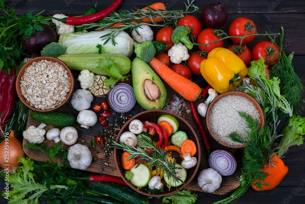 A mixture of vegetarian food for the Mediterranean diet. View from above. Photographed on a dark wooden background.