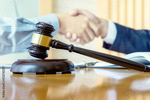 Photo Lawyer or judge gavel with balance handshake with client