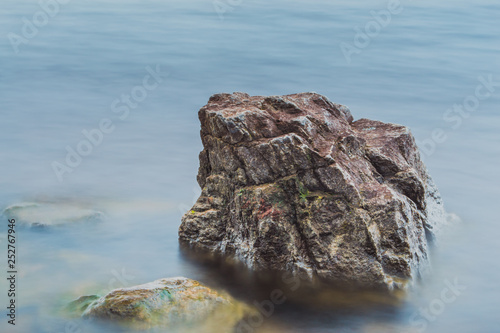 Photographie  Stone in the water. Long exposure of water and rock.