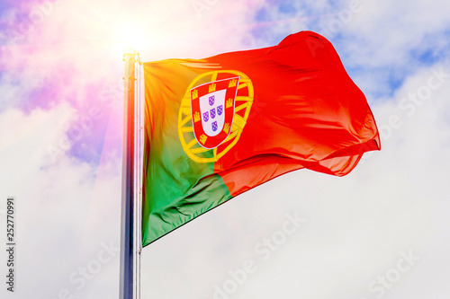 Foto  The national flag of Portugal flutters in the wind against a blue cloudy sky