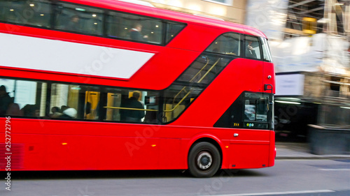 3745_One_of_Londons_red_bus_passing_by_the_street.jpg Fototapet