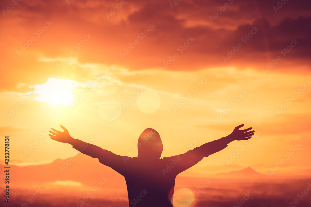 Fototapeta Copy space of man rise hand up on top of mountain and sunset sky abstract background.