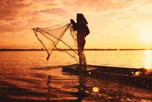 Asia Fisherman Using Net Fishing On Wooden Boat Casting Net Sunset Or Sunrise In The River