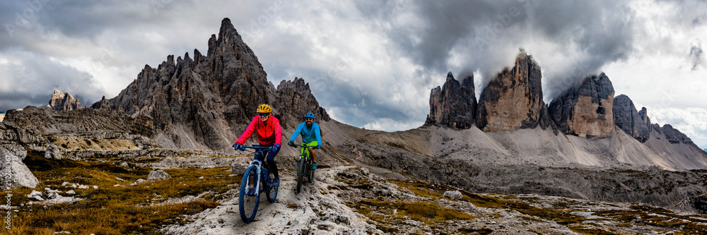 Fototapety, obrazy: Cycling woman and man riding on bikes in Dolomites mountains andscape. Couple cycling MTB enduro trail track. Outdoor sport activity.