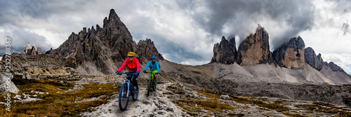 Fotografia Cycling woman and man riding on bikes in Dolomites mountains andscape