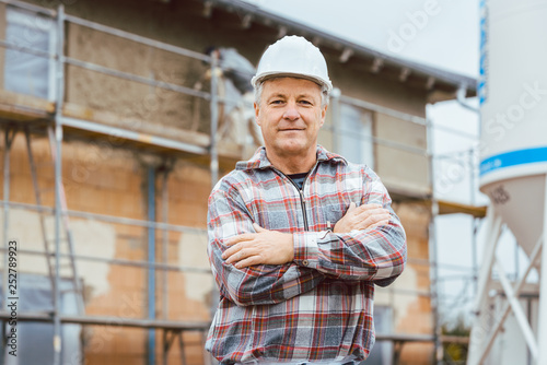 Proud plasterer standing in front of scaffold on construction site