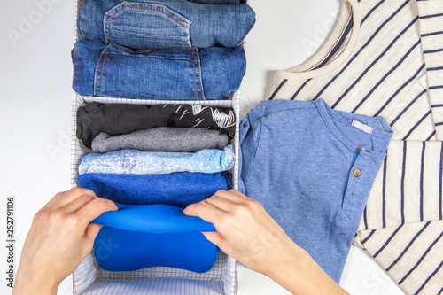 Fotografie, Obraz  Woman hands tidying up kids clothes in basket