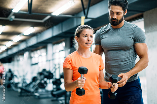 Young beautiful woman doing exercises with personal trainer Fototapete