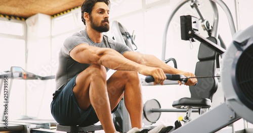 Poster Fitness Fit man training on row machine in gym