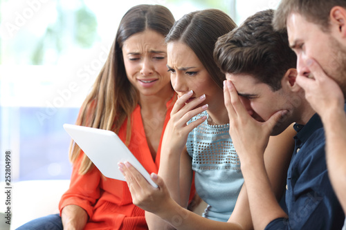 Worried friends checking tablet online news at home