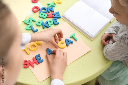 Little girl with speech therapist composing words of letters in office Canvas Print