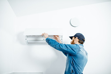 FototapetaRepairman in blue workwear serving the air conditioner changing filter on the white wall background