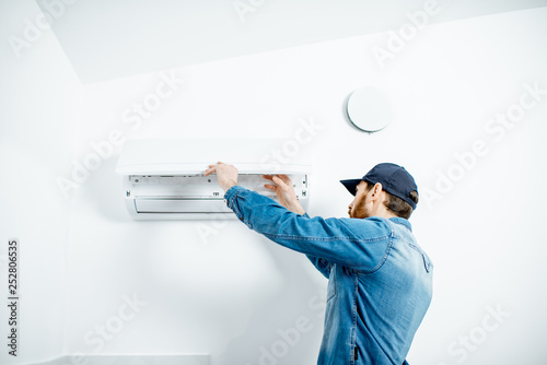 Fényképezés Repairman in blue workwear serving the air conditioner changing filter on the wh