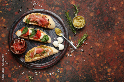 Plate with fresh tasty bruschettas on color background
