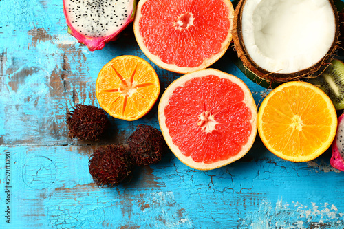 Fotografia Assortment of exotic fruits on color wooden background