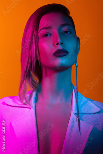 Foto op Plexiglas Beauty In the club concept. Fashion portrait of rich glamourous woman wearing luxurious earrings, posing over orange background. Pink, blue neon lights. Close up. Synthpop style. Studio shot