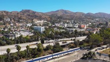 A Drone Aerial Of The Pacific Surfline Amtrak Train Passing Through The Southern California Beach Town Of Ventura, California With Freeway Foreground And Mountains Background.