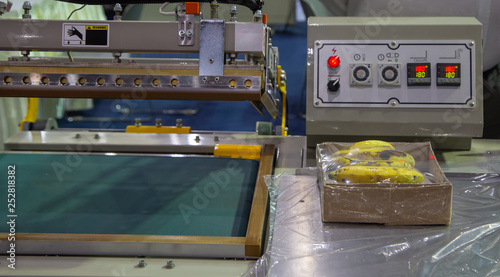 Photo  Industrial plastic shrink wrapping machine packing a carton of banana