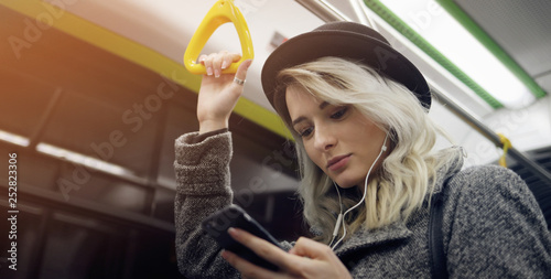 Fotografie, Obraz  Happy female passenger listening to music on a smartphone in public transportation