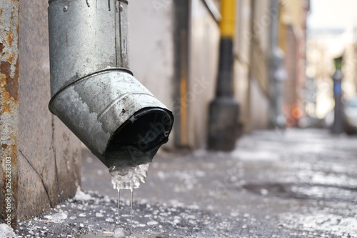 Fotografia, Obraz  Metal drain pipe with frozen water in winter on Moscow street